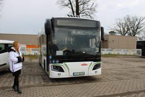 Księgowa MPK stoi przy autobusie elektrycznym.